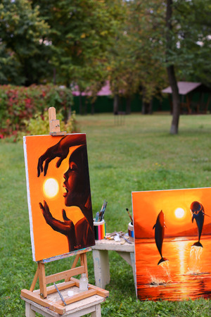Photography and fine art paintings executed in warm shades of orange. One painting shows girl who holding sun between hands,  second drawn dolphins jumping out of  water at sunset. Pictures standing in park on background of lawn in daylight.Concept of art