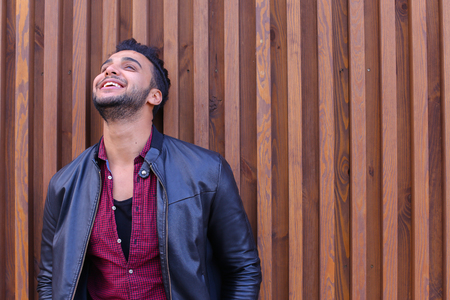 corrects: Engaging Young Adult Arabian Male Man, Businessman, Student Smiles and Laughs, Posing For Camera and Winks, Looks Forward on Sides, Waits Meeting, Corrects Hairstyle and Recalls Something Good Stands Near Wood-Paneled Walls in Open Air. Confident Guy Arab Stock Photo
