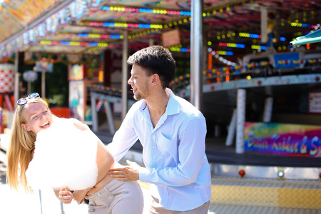 Beautiful young people, loving couple strolling in amusement park, looking at each other, kissing and cuddling, try candy floss, pose for camera and fooled at an amusement park outdoors. Girl with long blond hair and sunglasses dressed in white top and be Stock Photo
