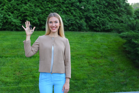 broadly: Charming Lady European appearance rejoices acquisition machine or your own apartment, overflowing emotions girl smiling broadly and showing keys. Women with long blonde hair dressed in bright blouse, beige jacket and blue pants, standing on background of
