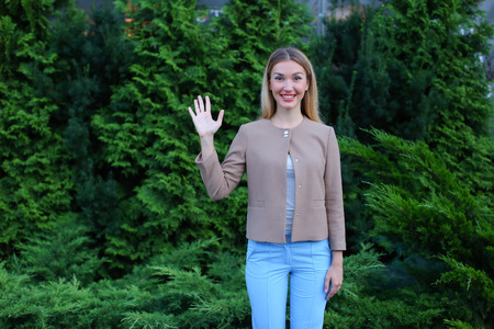 Nice girl smiling and showing gesture of «high five» or greeting, enjoys life and new day. Women with long blonde hair is dressed bright blouse, beige jacket and blue pants, stands on background of green grass and coniferous plants outdoors. Concept of