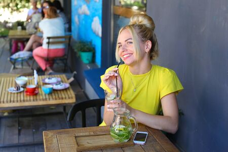 broadly: Stunning cute young girl female woman smiling broadly, holds glass in hand, drinking lemonade from straw, looks away, laughing and sits at wooden square table against background of gray walls and windows, wall with pattern and people in coffee shop outdoo Stock Photo