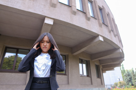 work took: Pretty young perspective business woman, student holds on head from fatigue, rests, took break from work and stands on background of abstract  business center on street in open air. Woman with black hair, dressed in white blouse and classic jacket with bl Stock Photo