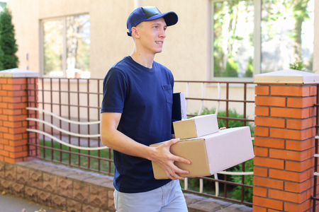 Messenger Carring Two Boxes in Hands Smiling on Background of Trees Along Street. Courier Company Provides Its Services in All Areas Ofterrain, Man of European Appearance in Uniform Carries Two Boxes With Order Along Street on Background of Shrubs, Trees  Stock Photo