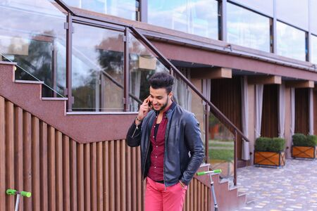 despacio: Confident Attractive Young Guy Muslim Businessman Goes Slowly Along Wall, Holding Phone in Hand and Talks, Resolve Issues, Discuss Future Plans and Smiling, Holds Hand in Pocket, Stands on Background of Wooden Panel Stairs Near House Outdoors. Bearded Man