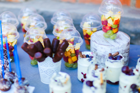 In photo depicts variety of goodies, delicious food, clear jars with cottage cheese soufflé with layer of pastry topped with fruit and straws, chocolate long candy skewers in patterned white small vase, chocolate balls in coconut flakes with blue straw Stock Photo
