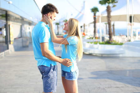 Couple in love, young man and woman, cute smiling, stand and gently hugging each other on background of sea, tall palm trees and umbrellas on sunny embankment outdoors. Girl with long blond hair dressed in bright blue shirt, and blue denim shorts, guy wit