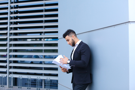 considers: Perspective young adult businessman virile asian guy holds and looks, considers, reads and sorts out papers or documents, stands near gray wall of business center. Bearded man dressed in classic suit, black pants, jacket , white shirt, on hand is watch. C Stock Photo