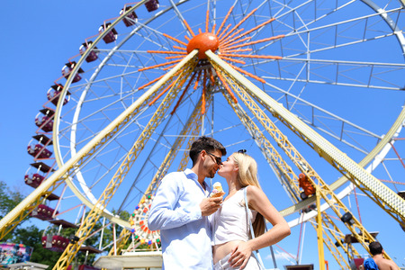 Cute young people, newlyweds kissing, hugging and smiling, looking into eyes of each other and posing for photos, guy holding ice cream on background of large and colorful ferris wheel at an amusement park outdoors. Girl with long blond hair dressed in br