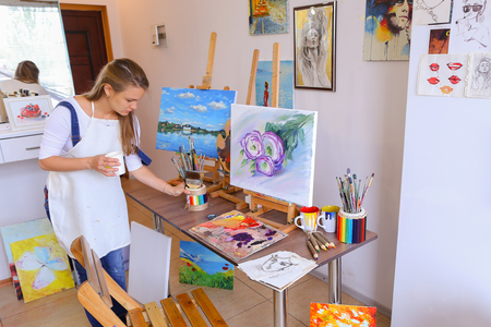Charming female woman painter removes workplace, table on which stands easels with paintings and appraising looks at picture, which painted and stands in  art studio against white wall on which hung variety of pictures and sketches. Girl dressed in white  Stock Photo