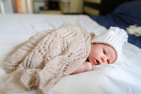 cognicion: Small newborn baby boy covered beige knitted blanket and dressed in white knitted cap with bubo and which lies on white bed in sleeping room. Concept of Maternal Love, Affection, Beginning Life, Cognition Surrounding World. Foto de archivo