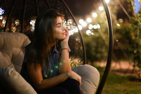 expects: Beautiful young and modern woman resting outside in restaurants and sitting in chair suspended on background of glowing lights. Girl dreamily lost in thought and expects evening gatherings with friend outdoors summer warm evening.Concept of beautiful succ