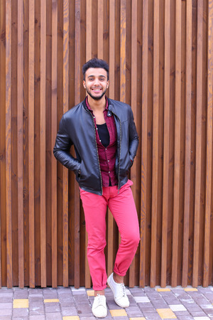 broadly: Man Muslim appearance standing and enjoys life, smiles broadly and looks forward to important meeting, smiling man posing and shooting for advertising mens contemporary clothing on background of wooden wall panel near restaurant outdoors. Male dressed in