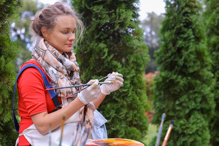 Artist cleans workplace, evaluate work that stands on easel, smiling, posing and looking in camera, sits on chair in park outdoors on background of coniferous plants in afternoon. Girl dressed in red sweater, dark jeans, white apron and checkered scarf ar