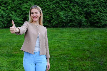 Slender blonde smiles and shows gesture of Cool, enjoying life and new day, advertises and shows evaluation of cosmetic product, recommends beauty salon or restaurant. Women with long blonde hair  dressed in bright blouse, beige jacket and blue pants, s