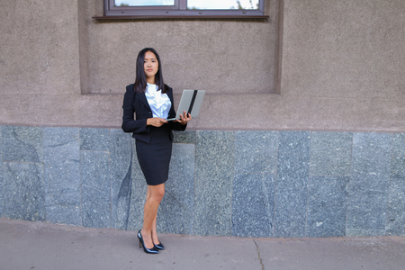 promising: Promising young entrepreneur beautiful woman uses laptop for work, make appointment, solves important business issues and and stands right in all growth against the background of gray wall of business center. Woman with black hair, dressed in white blouse