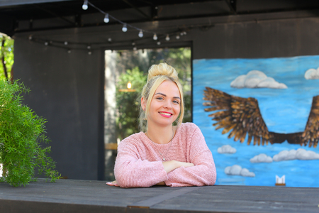 broadly: Lovely young adult female woman smiles broadly, looks and posing at camera, sits at wooden table on gray background panoramic windows, walls decorated with pictures and garland of lanterns. Girl with blond hair dressed in pink knitted sweater. Concept of