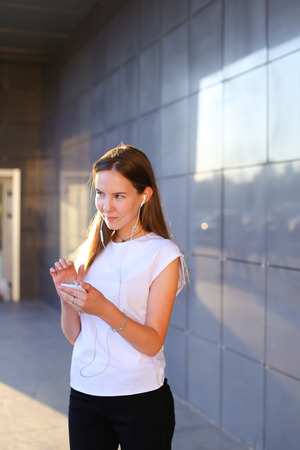 bl: Business attractive girl young business woman holds white telephone, listens to music, uses phone to work, solves problems, smiles and looks aside on background of gray wall of business center. Girl with long light brown hair dressed in white shirt and bl Stock Photo