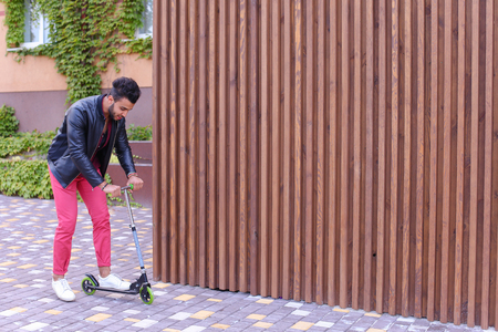 Handsome Young Muslim Arabic Man, Student Rides on Gray Scooter, Fun, Learn to Ride, Advertises Scooter on Background of Wooden Panel Stairs Outdoors. Bearded Man With Dark Hair Dressed in Black T-Shirt Over a Maroon Shirt and Wears Black Leather Jacket,