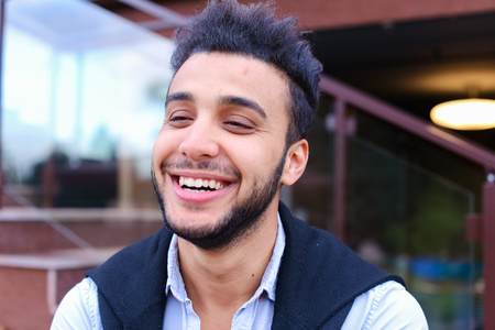 Portrait of beautiful Arab guy. Happy young man smiling big smile and looking in camera removed for advertising toothpaste or shampoo, stands on background of restaurant outdoors. Concept male cosmetics advertising, well-groomed guy healthy teeth and smil
