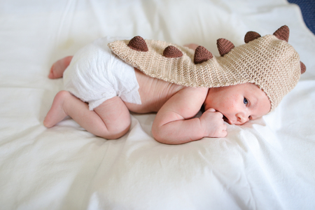 cognicion: Newborn boy in funny brown knit dragon suit lies on white bed in bedroom. Concept of Maternal Love, Affection, Beginning Life, Cognition Surrounding World.