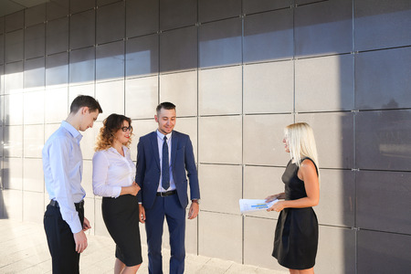 explains: Beautiful young ambitious girl in black dress holds paper and explains, makes remarks, explains adjustments in documents, share information and advice with colleagues, who listen, contribute their ideas and stand on wall background of business center outd