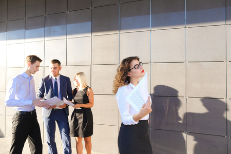 work took: Pretty young perspective business woman, student rests, took break from work, holds paper and waving them, watching and stands on background of colleagues who discuss workflows, consider paper near of business center on street. One of guys dressed in blue Stock Photo