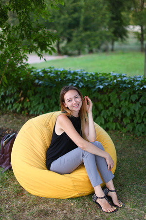 Attractive female enjoying holiday in yellow soft and comfortable chair and poses for photo on background of green plants outdoors in sunny park hot day. Student after school or work decided to look for some fresh air spring day in open air. Girl of Europ