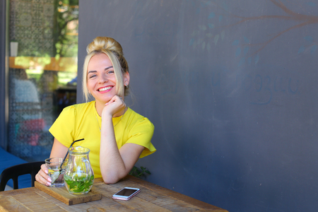 broadly: Stunning cute young girl female woman smiling broadly, holds glass in hand, looks at camera, laughing, sits at wooden square table against background of gray walls and windows in coffee shop outdoors. Girl with blond hair dressed in short citric dress.Con Stock Photo