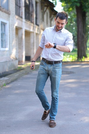 Bearded young men man guy goes, walking along road and looking at watch on arm. Young man dressed in white shirt with red stripe, blue jeans and brown loafers. Concept of business man waiting for meeting, posing in front of camera, casual style.