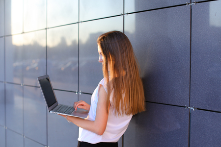 hait: Young successful woman entrepreneur girl keeps in hands computer and  works, typesets text, resolves issues stands sideways to camera on background of wall of business center. Girl with long hait dressed in white shirt and black trousers.Concept of busine Stock Photo