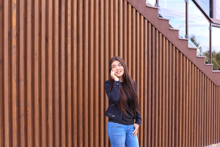 Cute girl with long hair cute talking on phone with friend or loved one, make an appointment. Women dressed in black sweater, blue jeans, black boots on platform and top dressed in jacket standing on background of brown wood panel walls near restaurant ou