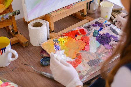 Women Artist extrudes hands in white gloves oil paint from tubes on multi-colored palette for viewing and mixing colors to start drawing pictures in art studio. On table stands glass of water, jar of colored pencils and brushes and palette sketch. Concept Stock Photo