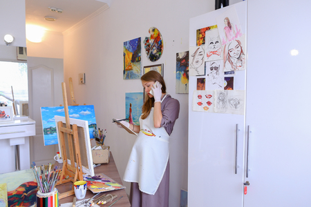 communicates: Lovely Female Painter Orders Things to Draw or Picture Frames , Clarifies Meeting With Students For Master Class, Communicates With Clients About Sale of Paintings. Woman With Long Light Brown Hair Dressed Sht Pale Purple Jacket, White Apron and White Glo