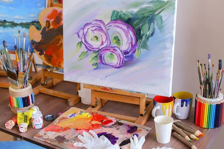 canvas print: Photo works of art, drawing with purple flowers on white canvas on easel written by artist in art studio. Concept of picture written by oil, hobbies and passions, talented peopleadvertising art supplies or school.