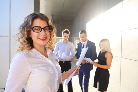 work took: Pretty young perspective business woman, student rests, took break from work, holds paper and waving them, watching, smiling and posing at camera and stands on background of colleagues who discuss workflows, consider paper near of business center on stree
