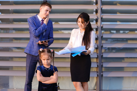 frowns: In  foreground stands and frowns, angry with arms crossed in front of little girl, child,  in background successful young handsome mans man, young father and modern woman, young mother hold gadgets in hand, mobile phones and talking to them, solve operati Stock Photo