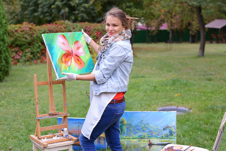 Female European appearance artist evaluates picture and removes from easel, holds and posing with picture which depicts colorful butterfly, smiling and standing in full growth on background of lawn and angered by conifers in large park in open air. Girl d