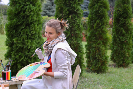 smeared: Pretty attractive artist begins to or finishes drawing sitting right in front of to photographer and behind wooden easel, holds palette smeared in paint in large green park day outdoors.Girl with brown hair collected in beam dressed in light jacket, red j