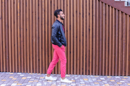 Handsome Young Adult Muslim Man, Businessman Walks Slowly Along Stairs, Looks Around and Smiles, Holds Hands in Pockets of Jackets, Advertises Clothing on Background of Wooden Stairs Near Restaurant Outdoors. Confident Arab Guy With Dark Hair Dressed in B