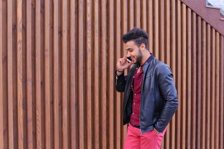 Seguros de negocios joven atractivo individuo musulmán se desplaza lentamente largo de la pared, sosteniendo el teléfono en la mano y conversaciones, resolver problemas de, discutir los planes futuros y sonriente, tiene la mano en el bolsillo, está en el fondo del panel de madera escaleras Cerca de Casa al aire libre. Hombre barbudo