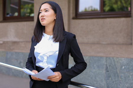 Pretty female girl student holds in hands important paper, Students work or homework, constitutes plan and stands against backdrop of modern business center.Woman with black hair, dressed in white blouse and classic jacket with black skirt and heels.Conce Stock Photo