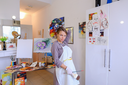 Cute female painter posing, laughing and fooling around in front of camera and smiling with brushes and colorful palette in hand, standing in studio with white art paintings on walls. Girl European appearance advertises art school for adults and children,