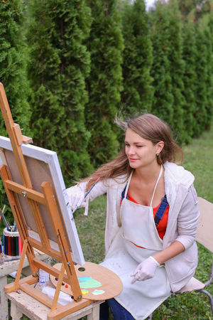 Female artist holds brush and wrote oil on canvas painting, does what likes, interests and hobbies,  preparing picture to order, advertises or art studio for drawing utensils, sits on chair at  wooden easel in large green park outdoors. Girl with brown ha