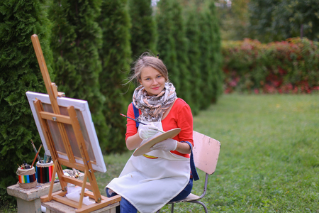 ch: Cute female painter posing, laughing and in front of camera , draws and smiling with brushes and colorful palette in hand, sits on chair near easel in green park outdoor.  Girl with brown hair dressed in red jamper, dark denim overalls and white apron, ch