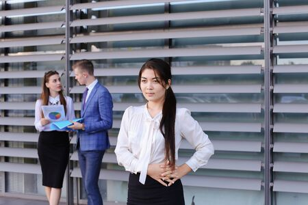 work took: Successful young adult  business lady, student rests, took break from work, watching, smiling and posing at camera and stands on background of colleagues who discuss workflows, consider paper near of business center outside. Girls with light brown and dar Stock Photo