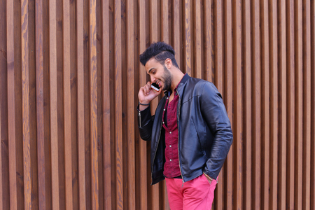 Confident Attractive Young Guy Muslim Businessman Goes Slowly Along Wall, Holding Phone in Hand and Talks, Resolve Issues, Discuss Future Plans and Smiling, Holds Hand in Pocket, Stands on Background of Wooden Panel Stairs Near House Outdoors. Bearded Man
