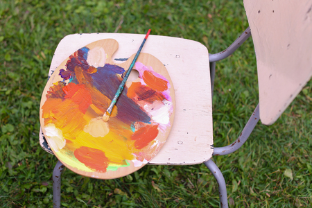 Photo of Wooden palette with paints which lying on chair with brush located in park outdoors. Concept of art materials, oil or acrylic paint, professional artist items, hobbies and advertising brand of paints or brushes.