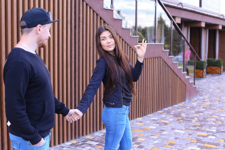 where to go: Lovers of heart walk past restaurant and going to go to dinner, holding hands and talking, share secrets and jokes, decide where to go to have fun. Guy dressed in black sweater, blue jeans, sneakers and black cap, girl with long black hair dressed in blac