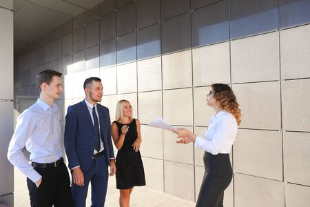 explains: Beautiful young ambitious girl in white blouse holds paper and explains, makes remarks, explains adjustments in documents, share information and advice with colleagues, who listen, contribute their ideas and stand on wall background of business center out